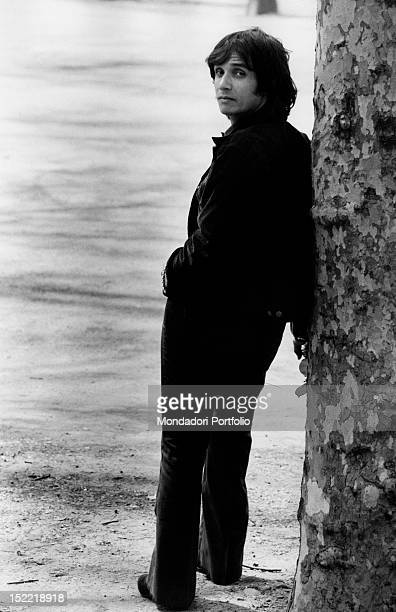 The Brasilian singer Roberto Carlos is leant against a tree looking back toward the photographer Milan 1970