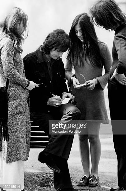 The Brasilian singer Roberto Carlos is sat on a park bench signing autographs for some of his fans Milan 1970