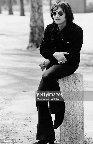 The Brasilian singer Roberto Carlos is wearing sunglasses and is sat on a small column Milan 1970
