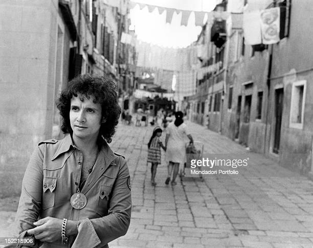 The Brasilian singer Roberto Carlos posing in a Venetian 'calla' in the background you can see the street with hanging clothes from a window to...