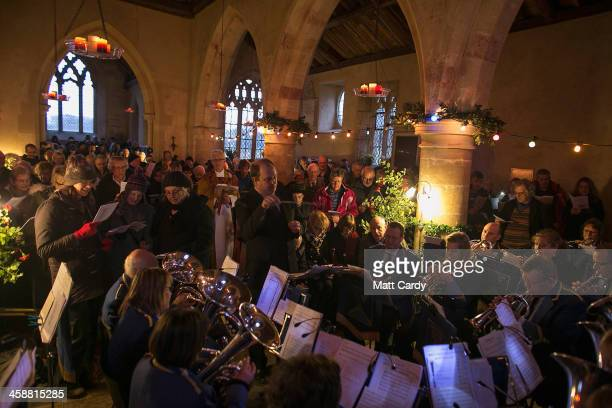 The Bratton Silver Band performs as people sing Christmas carols at the fifth annual carol service being held inside the 13th century St Giles church...