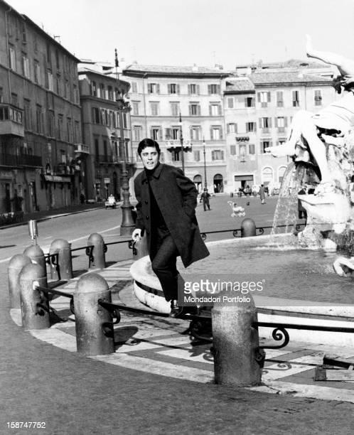 The Brazilian musician and composer Chico Buarque jumping the parapet of the Fontana dei Quattro Fiumi in Piazza Navona Rome 1969