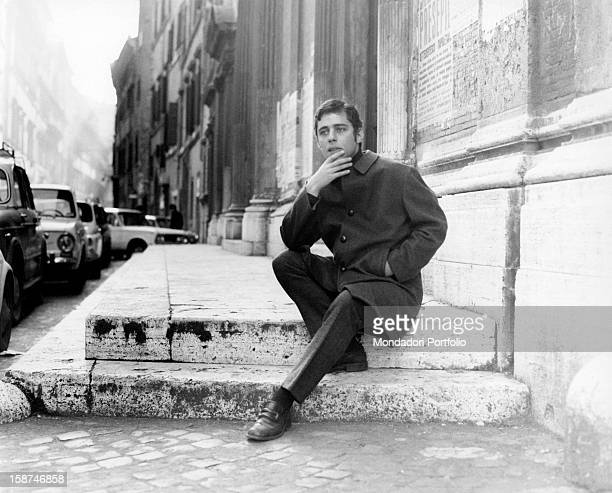 The Brazilian musician and composer Chico Buarque sitting on the parvis of a church Rome 1969
