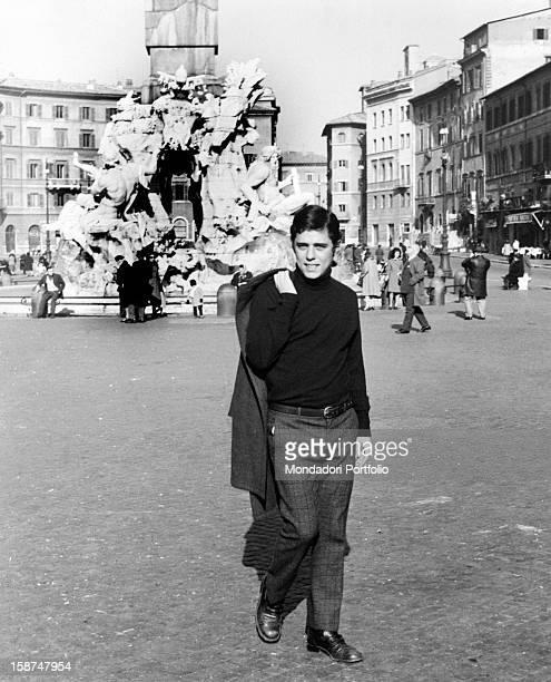 The Brazilian musician and composer Chico Buarque walking through Piazza Navona leaving behind him the Fontana dei Quattro Fiumi Rome 1969