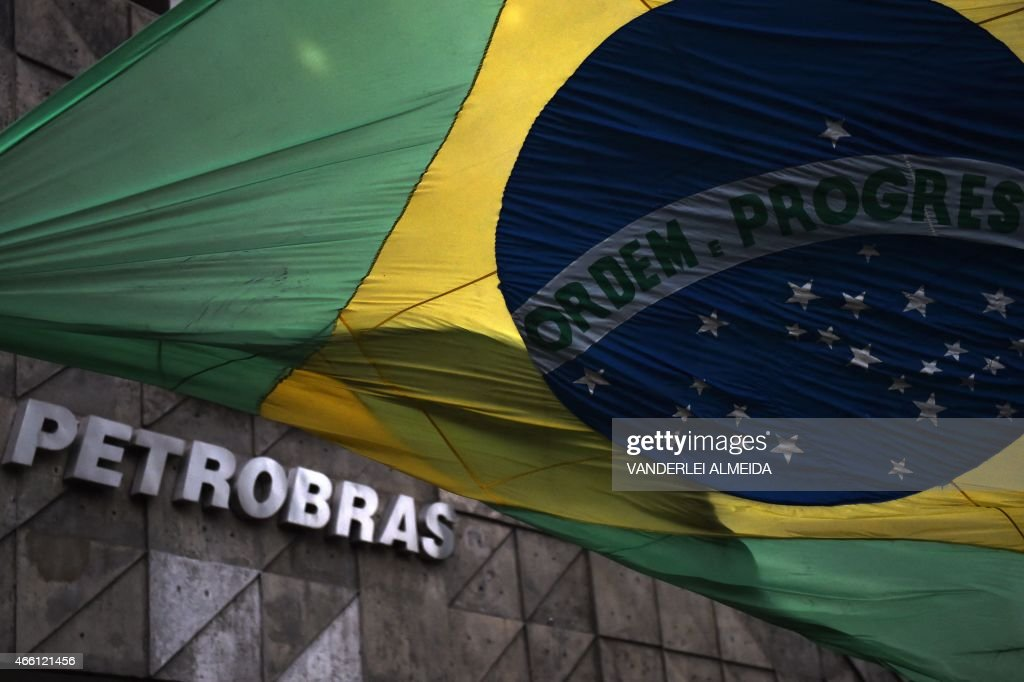 The Brazilian national flag flutters at the front of the headquarters of the Brazilian state oil giant Petrobras, in Rio de Janeiro, Brazil, on March 13, 2015. The corruption scandal enveloping Brazilian state oil giant Petrobras deepened Thursday when prosecutors said they will investigate three members of the ruling coalition, including the governor of Rio de Janeiro state. Dozens of political figures and former Petrobras executives are under suspicion over a scheme facilitating corruption and money laundering that saw an estimated $3.8 billion creamed off inflated contracts over a decade, though nobody has yet been convicted.