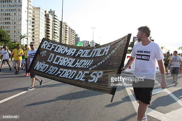 The Brazilian people on the streets to protest against the government and corruption The protesters carry flags of Brazil and banners with words and...
