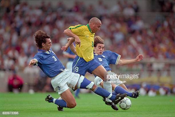 The Brazilian soccer player Ronaldo breaks through the Italian defense Fabio Cannavaro and Paolo Maldiniduring a French Tournament match which...