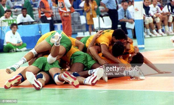 The Brazilian volleyball team pile on top of each other 09 August 1992 after defeating the Dutch team to win the gold medal at the 1992 Summer...
