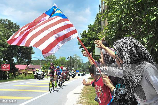 The breakaway composed of Lukas Jaun Shiki Kuroeda and Burr Ho passing in front of a Malaysian family during the fourth stage of the Tour de Langkawi...