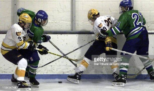 The Breck and Breck hockey team members mix it up in attempting to control the puck in first period action From left to right is Breck Colin Hohman...