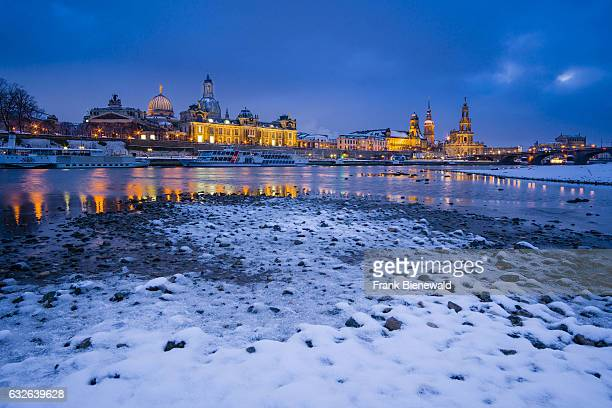 The Brühl Terrace Secundo Genitur Catholic Court Chapel and the Church of our Lady illuminated seen across the river Elbe in snow