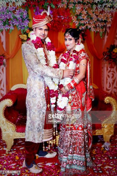 the bride and groom at the indian wedding garlands or jaimala ceremony - indian wedding stock pictures, royalty-free photos & images