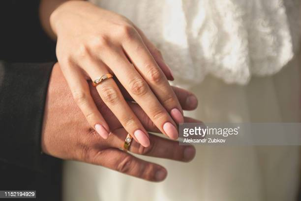 the bride and groom holding hands. wedding theme. close up. - newlywed stock pictures, royalty-free photos & images