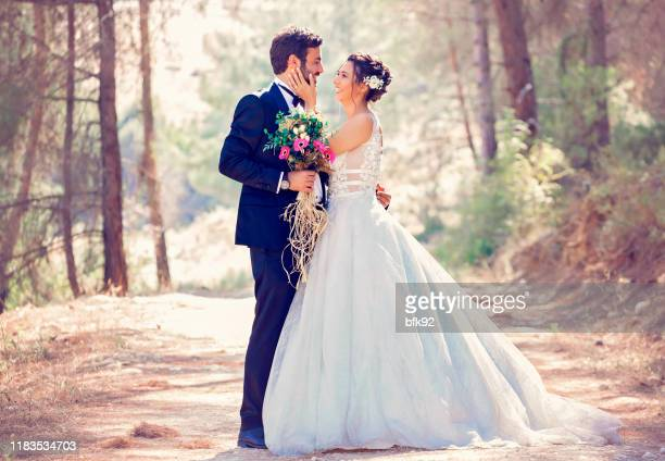 the bride and groom posing in nature. - wedding ceremony stock pictures, royalty-free photos & images