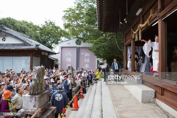 The bride and groom throw rice cakes after holding a wedding at Yanabe Hachiman Shrine The gesture symbolises sharing happiness and abundance This...