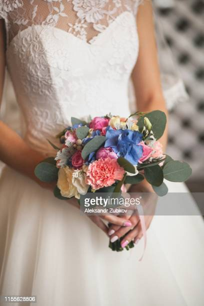 the bride in a white elegant wedding dress is holding a beautiful wedding bouquet of different flowers and green leaves. wedding theme - wedding background stock pictures, royalty-free photos & images