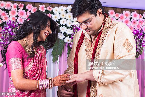 the bride inserting diamond ring in groom's finger - ceremony stock pictures, royalty-free photos & images