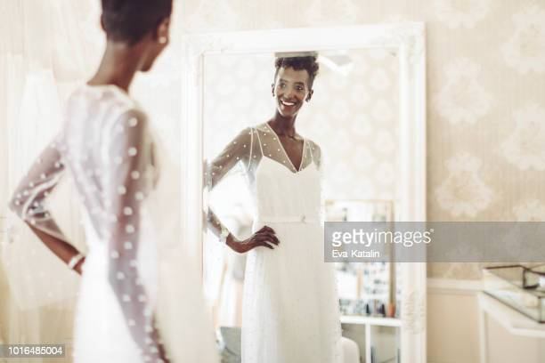 the bride is checking out her wedding dress - wedding dress stock pictures, royalty-free photos & images