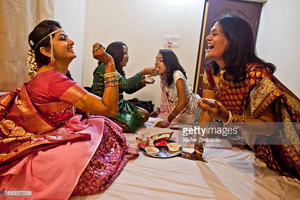 The bride playing with her aunt sister and her friends and eating rasogullas and other sweets at The Art of living International centre Ashram on...