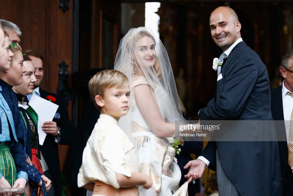 The bride Princess Maria Theresia von Thurn und Taxis is guided by her brother Prince Albert von Thurn und Taxis to the St. Joseph church prior to the wedding ceremony on September 13, 2014 in Tutzing, Germany.