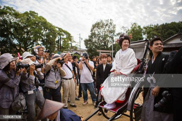 The bride seen riding in a rickshaw with the groom walking alongside during a traditional Japanese style wedding Many such traditional weddings are...