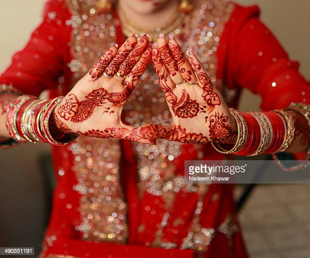 The bride with the hands painted with Mehndi at her wedding day