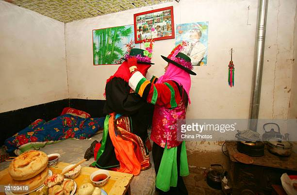 The bride's sister helps her to dress up before the groom's arrival during a Tu ethnic minority group wedding ceremony on January 30 2007 in Huzhu...