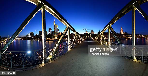 The bridge 'Eiserner Steg' and the skyline of Frankfurt with the skyscrapers illuminated at night pictured on June 26 2016 in Frankfurt Germany The...