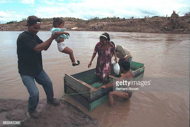 The bridge is down and people cross the Horo Agua in makeshift boats