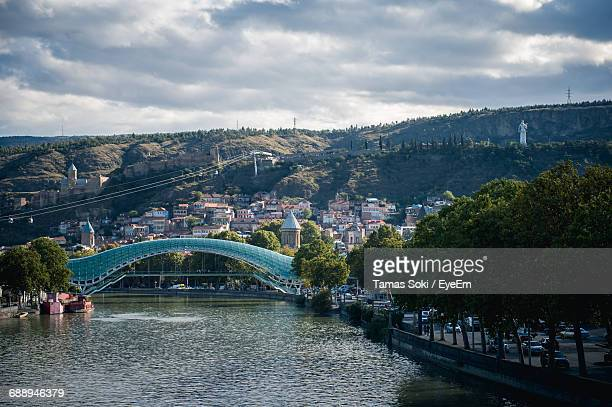 The Bridge Of Peace Over Kura River By Mountains Against Cloudy Sky