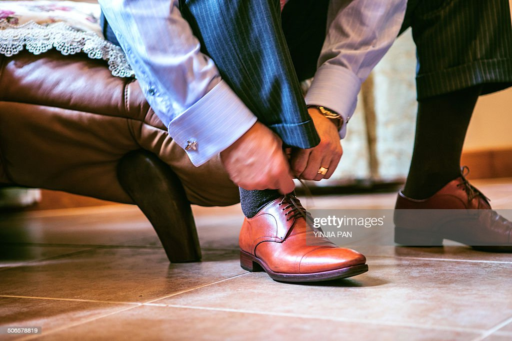 The bridgroom is wearing shoes : Stock Photo