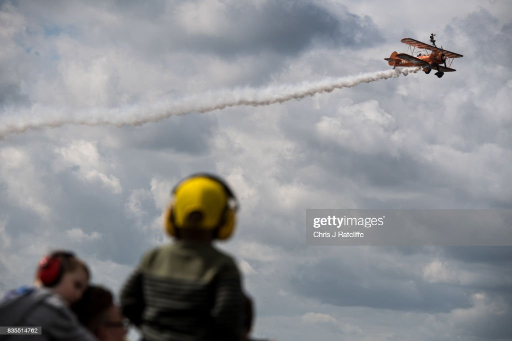 The Brietling Wingwalkers fly past children wearing ear defenders during a flying display at the Biggin Hill Festival of Flight on August 19, 2017 in Biggin Hill, England. The Biggin Hill Festival of Flight is an annual airshow event and in 2017 the airport is celebrating its centenary. The airport only became exclusively business and general aviation in 1959, prior to which it was used by the British Royal Air Force.