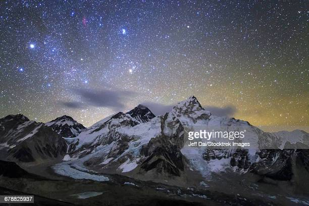 The bright stars of Auriga and Taurus rise above Mt. Everest and the central Himalayas.