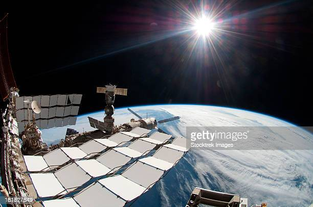 The bright sun, a portion of the International Space Station and Earth's horizon. The image was taken using a fish-eye lens attached to an electronic still camera.