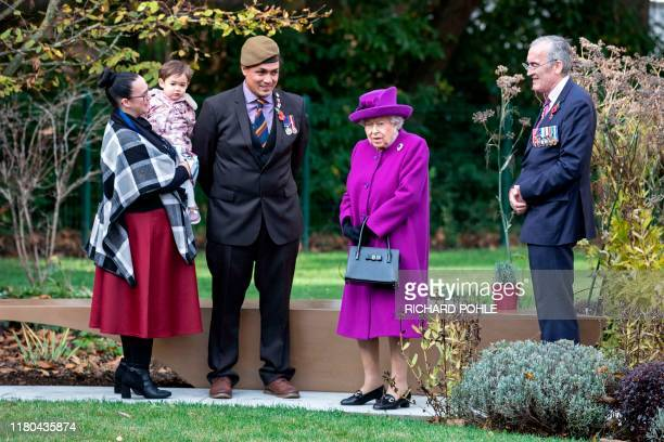 The Britain's Queen Elizabeth II stands in the new communal garden at the RBLI village in Kent with Gardener and veteran John Ahben from Fiji and his...