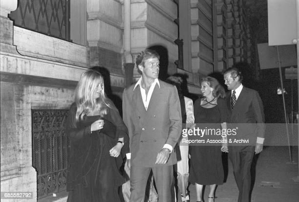The British actor Roger Moore and his third wife the italian actress Luisa Mattioli walking in the streets of Rome by night Rome June 1975