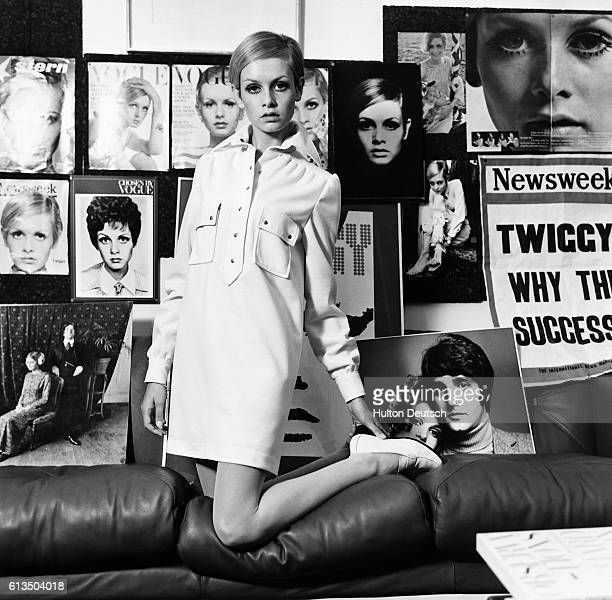 The British actress and model Twiggy, models a shirt dress amidst posters of her previous work, 1967.