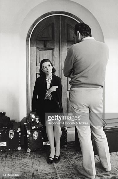 The British actress Audrey Hepburn sitting on a trunk speaking to Stanley Donen August 1966