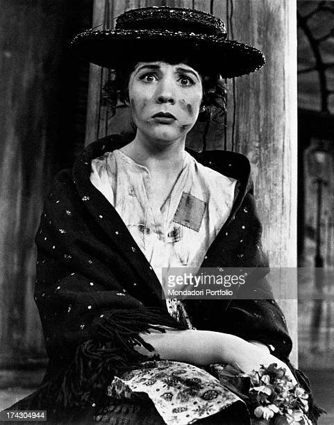 The British actress Julie Andrews the pseudonym of Julia Elizabeth Wells wearing a black hat and shall dirty with soot and with a sullen expression...