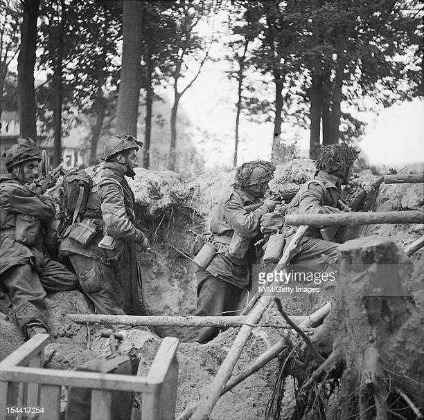 The British Airborne Division At Arnhem And Oosterbeek In Holland Men of the 1st Paratroop Battalion take cover in a shell hole 17 September 1944