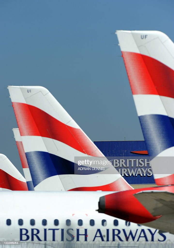 The British Airways logo is seen between tailfins of aircraft parked at Heathrow Airport, west of London, on May 24, 2010. Thousands of air travellers faced renewed travel chaos on Monday as British Airways cabin crew launched a five-day strike, after last-ditch negotiations collapsed. AFP PHOTO/Adrian Dennis