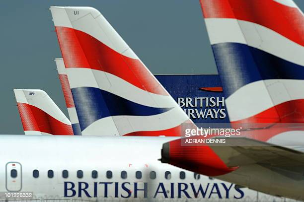 The British Airways logo is seen between tailfins of aircraft parked at Heathrow Airport west of London on May 24 2010 Thousands of air travellers...
