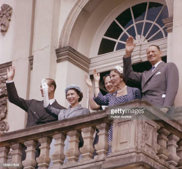 The British and Danish Royal family wave to the crowd from a balcony during the Queen's state visit to Denmark, May 1957. L-R; Prince Philip, Queen...