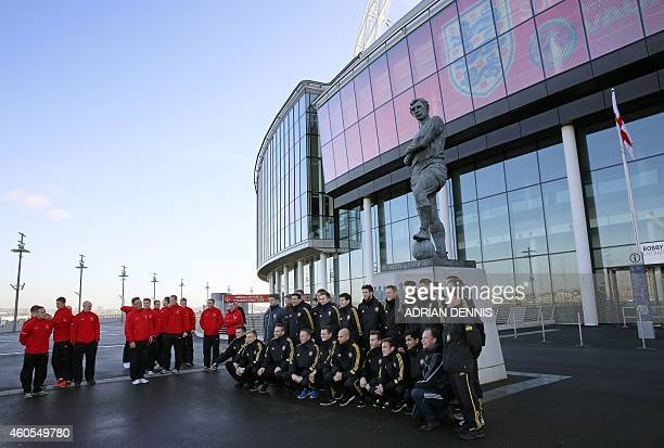 The British army football team in red looks on as the German team pose for a photograph beneath the statue of former England legend Bobby Moore...