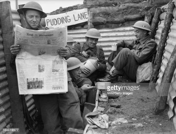 The British Army In France 1940, Men of the 1st Queen's Own Royal West Kent Regiment enjoy a tot of rum in a section of trench named 'Pudding Lane',...