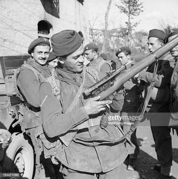 The British Army In Italy 1944, A Belgian commando inspects his rifle with sniper 'scope in a village at the foot of Mt Camino, 6 February 1944.