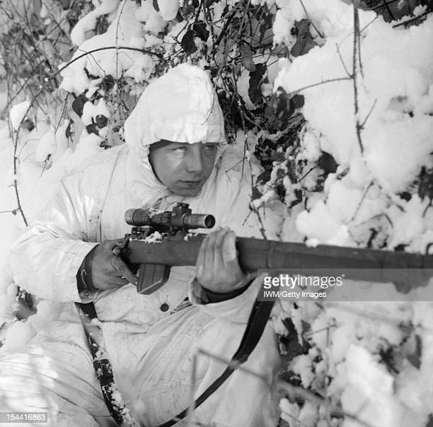 The British Army In NorthWest Europe 194445 A 6th Airborne Division sniper on patrol in the Ardennes wearing a snow camouflage suit 14 January 1945