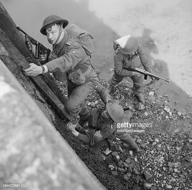 The British Army In The United Kingdom 193945 Men of the South Staffordshire Regiment armed with 'Tommy guns' climb up onto a harbour wall during an...