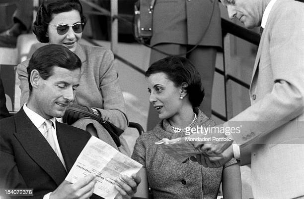 The British colonel and aviator Peter Townsend attends a race riding with Mrs. Tagliabue. Merano, 1955