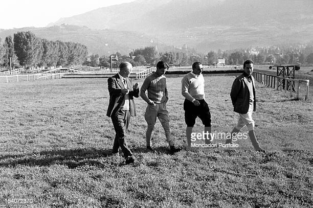 The British colonel and aviator Peter Townsend walking on a circuit riding with other men during an equestrian competition. Merano, 1955